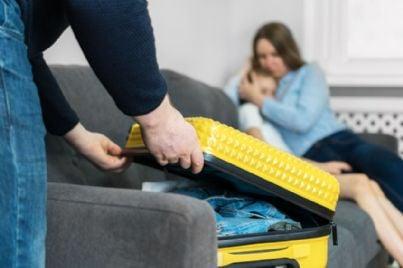 uomo fa le valigie di fronte a moglie e figlia tristi