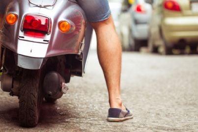 uomo con scooter che fa manovra in strada