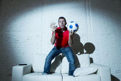 uomo con pallone e soldi in mano esulta per vittoria scommessa