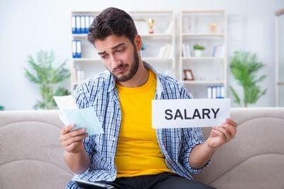 uomo triste con bollette in mano e salario magro