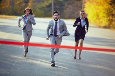 un uomo e due donne di affari che corrono per tagliare il traguardo