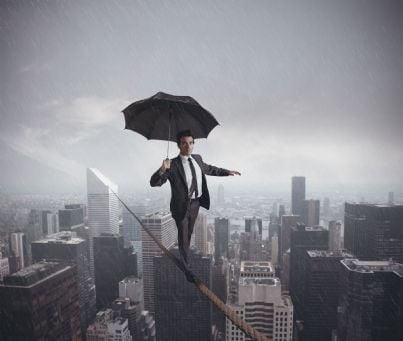 uomo di affari che si copre con un ombrello e sta in equilibrio su una corda