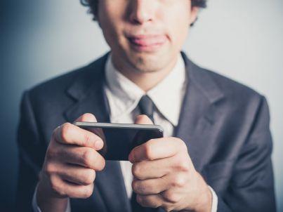 uomo di affari che gioca con il proprio telefono