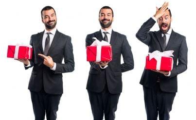 tre uomini affari con pacchi regalo in mano