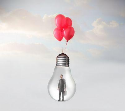 uomo affari sollevato da palloncini in una lampadina simbolo di salvezza fallimento