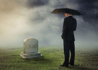 uomo affari davanti a tomba con scritto crisi