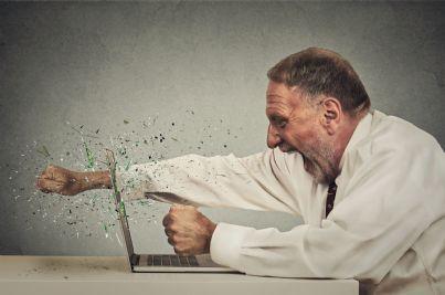uomo anziano arrabbiato tira pugno a computer