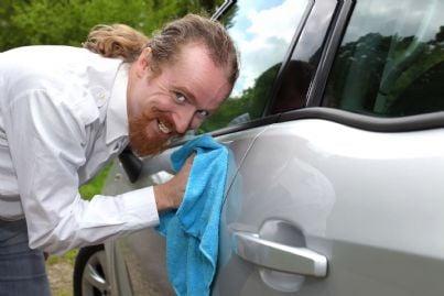 uomo che pulisce con un panno lo sportello auto