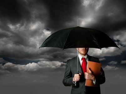 uomo di affari si protegge con un ombrello
