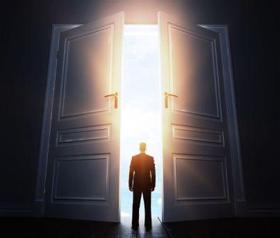 uomo che cammina verso una porta aperta con luce