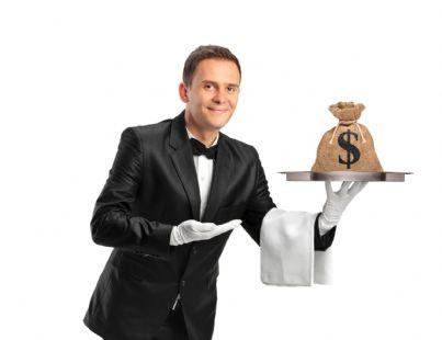 uomo vestito da cameriere che porge vassoio con sopra sacco di soldi