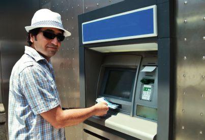uomo che effettua prelievo al bancomat