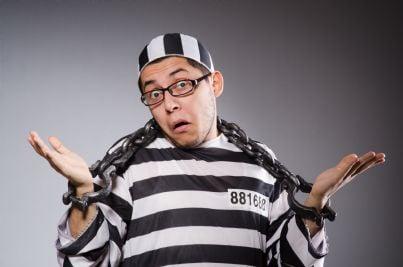 uomo in divisa da detenuto con manette