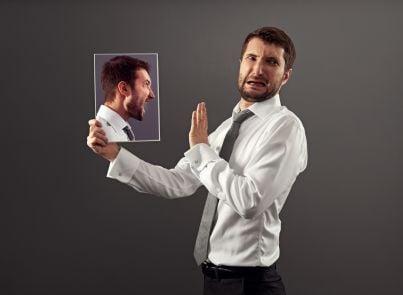 uomo ha discordia con se stesso allo specchio concetto autocalunnia