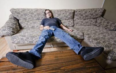 uomo pigro dorme sul divano con telecomando in mano