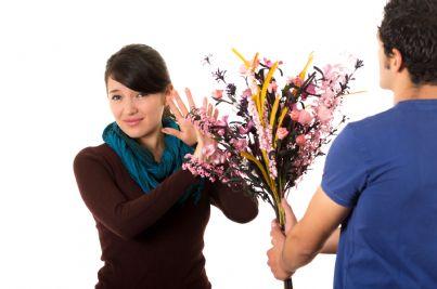 uomo che regala alla donna mazzo di fiori ma lei respinge