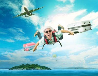 uomo che si lancia da un aereo con le valigie concetto vacanza