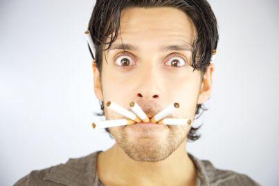 uomo con tante sigarette in bocca