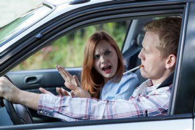 uomo fuma in auto e donna infastidita