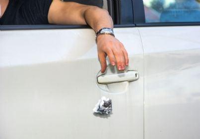 uomo che getta rifiuti dal finestrino della propria auto
