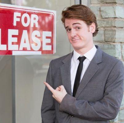 uomo mostra cartello affitto su vetrina negozio