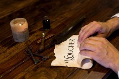 uomo rotola pergamena con su scritto voucher