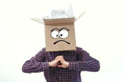 uomo con testa dentro una scatola con disegno perplesso