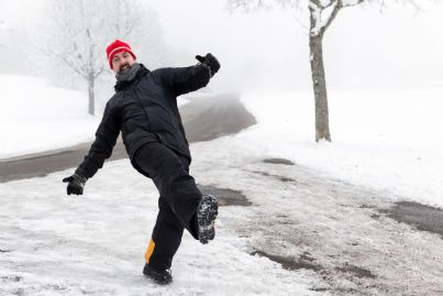 uomo scivola su strada ghiacciata