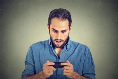 uomo guarda sorpreso il proprio cellulare