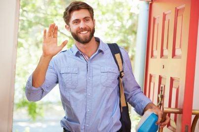 uomo che entra a casa sorridente