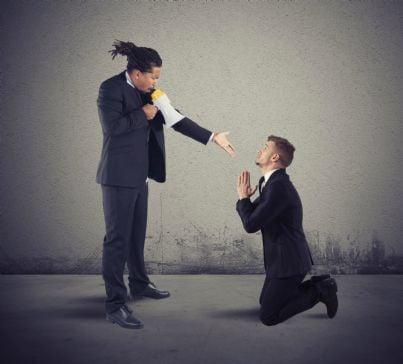 uomo sgrida un suo dipendente in ginocchio