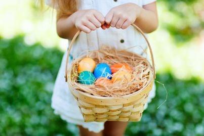 bambina su un prato con un cestino contenente uova pasquali