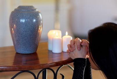 donna mostra dolore di fronte ad urna contenente ceneri cremate