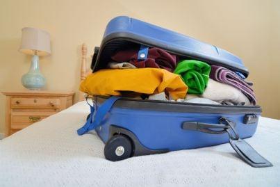 valigia piena su un letto di hotel