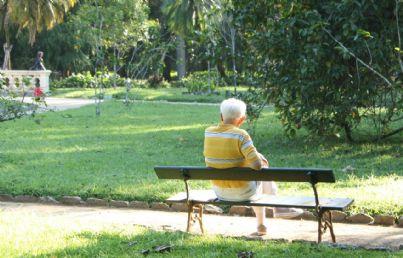 uomo anziano seduto da solo in un parco