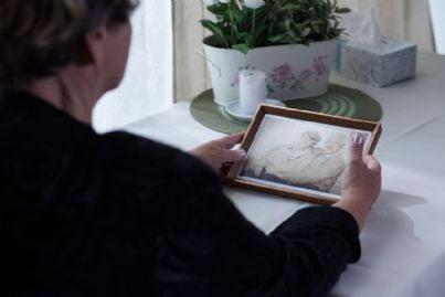 vedova che guarda la foto del marito