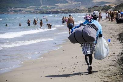 un venditore ambulante cammina sulla spiaggia