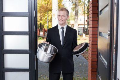 venditore sorridente mostra pentole porta a porta