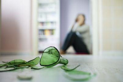 violenza domestica donna seduta con primo piano bottiglia rotta