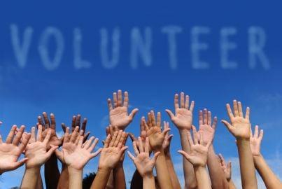 mani di volontari alzate al cielo