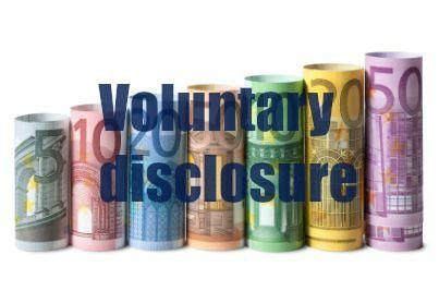 scritta voluntary disclosure e sullo sfondo delle banconote arrotolate