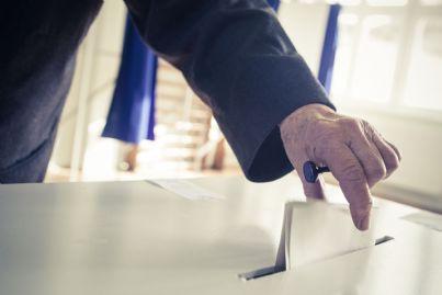 uomo inserisce scheda dopo aver votato