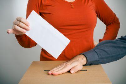 donna corrotta che vota e uomo che tenta di fermarla
