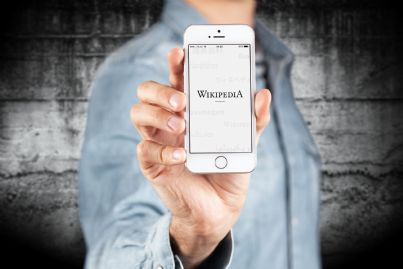 avvocato tiene in mano telefono con pagina wikipedia